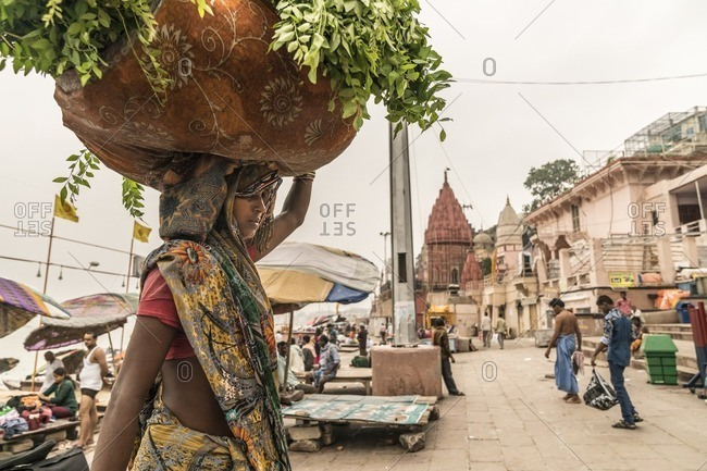 Varanasi, India - July 8, 2016: A woman walking with food for cattle on her head in Varanasi along the Ganges River