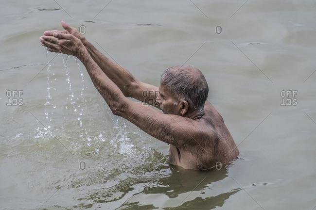 Varanasi, India - July 8, 2016: A Hindu man bathes and prays in the Ganges River, Varanasi
