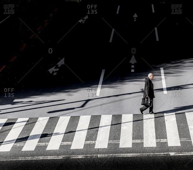 Tokyo, Japan - December 3, 2016: Businessman walking on crosswalk in Tokyo, Japan after work