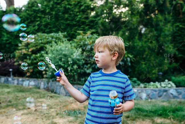Boy watching bubbles from wand