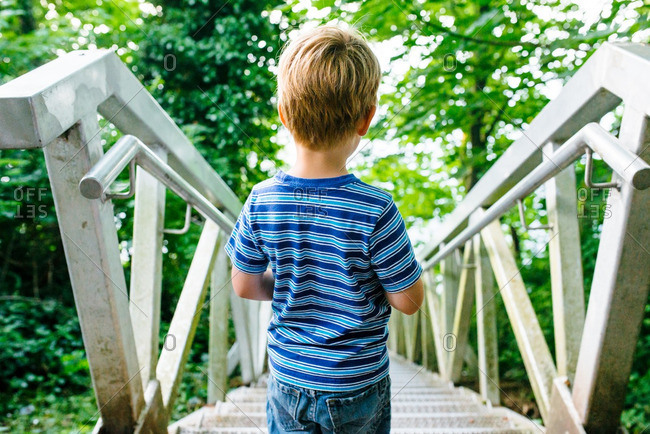 Boy looking down steps in country