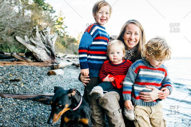 Mom and three boys on a beach