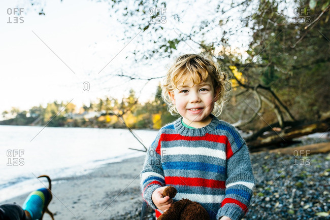 Boy in sweater smiling on beach