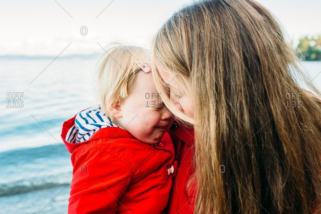 Mom soothing crying girl on beach