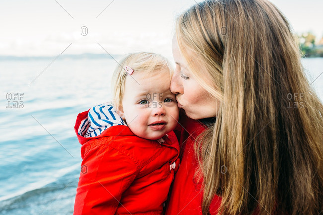 Mom soothing girl on beach
