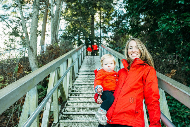 Mom holding toddler by rural steps