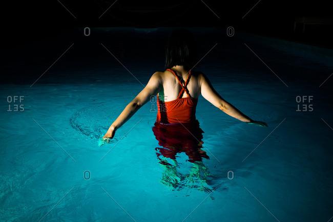 Woman in pool at night