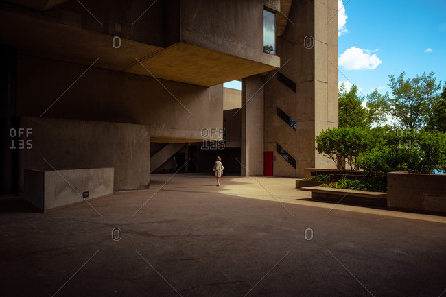Woman by modern concrete building