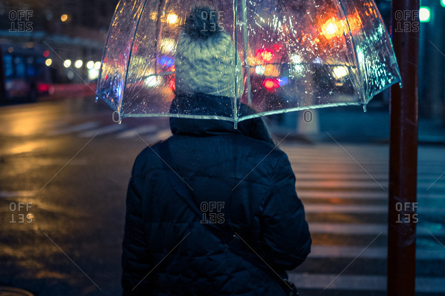Woman with umbrella in city at night