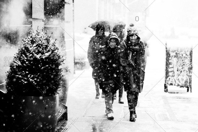 People walking in city snow fall