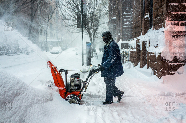 Man blowing snow from sidewalk, NYC