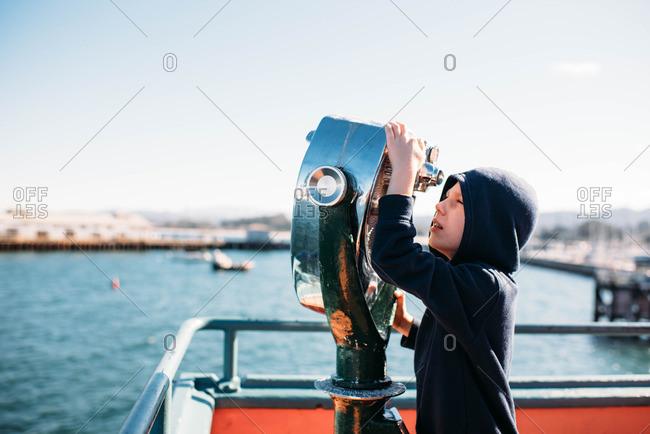 Boy looking through viewfinder by Monterey Bay