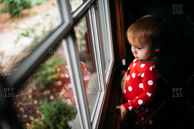 Toddler girl wearing red pajamas looking out a window