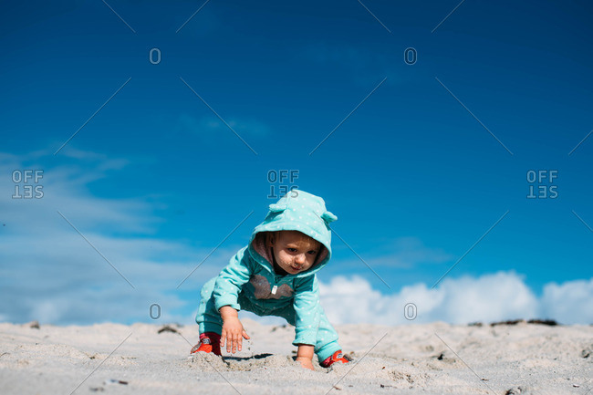 Toddler playing in sand on cold beach