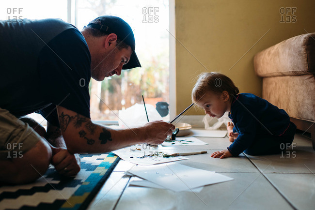 Father and toddler painting inside together