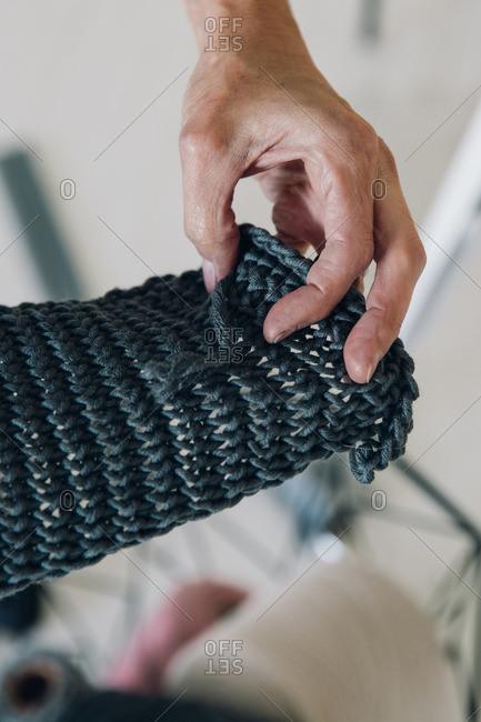 Woman hand holding piece of knitted fabric
