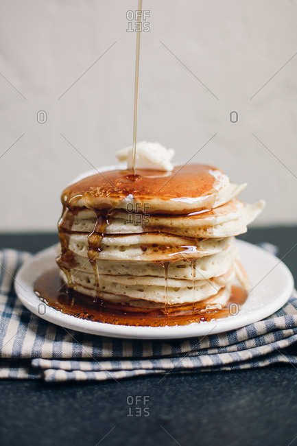 Stack of pancakes with syrup pouring over top