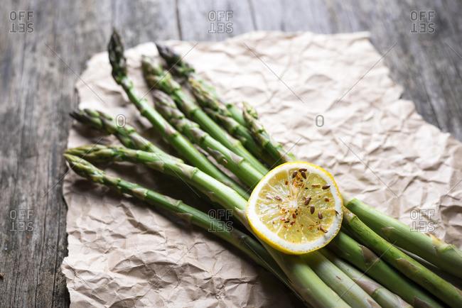 Fresh asparagus and lemon slice on craft paper