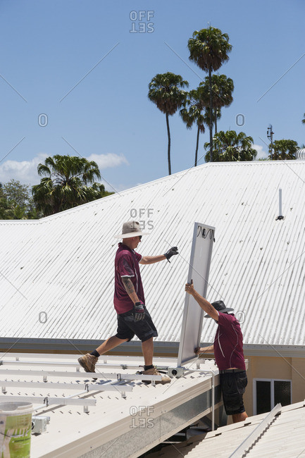 Two men working to install solar panels on a roof