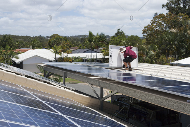 Man lifting a solar panel on a roof during an installation
