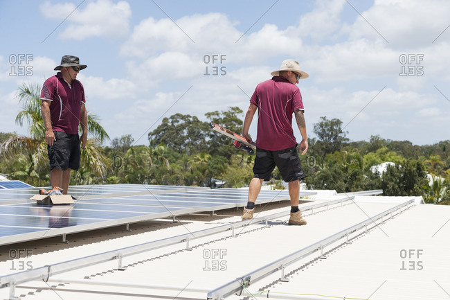Two men working on a roof to install solar panels