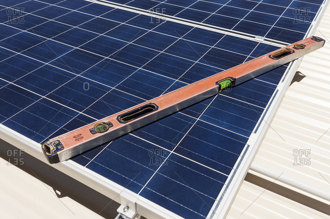 Level tool resting on a rooftop solar panel