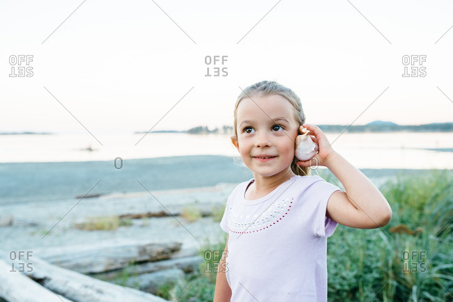 Young girl listening to a seashell
