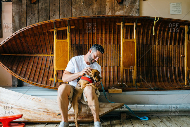 Man petting a dog in front of a boat