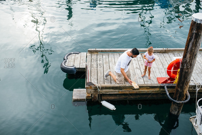 Father and daughter putting a wooden boat into the water