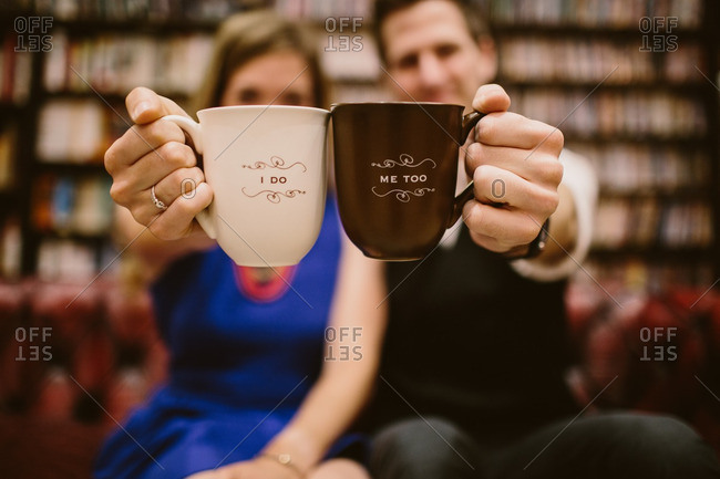 """Engaged couple holding coffee mugs that read """"I do"""" and """"Me too"""""""