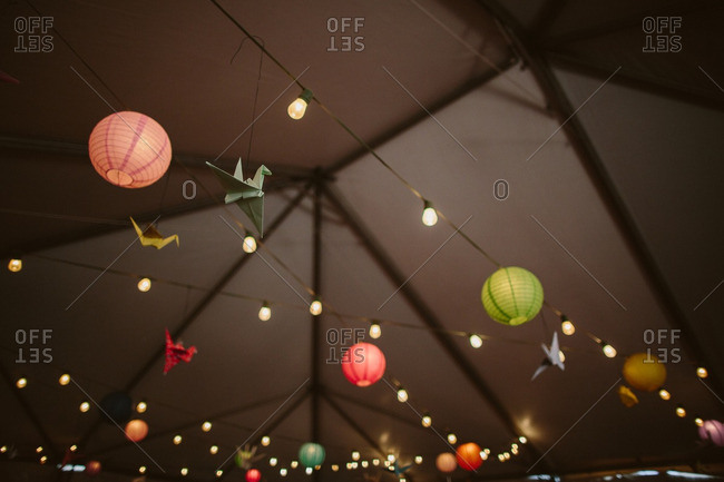 Origami birds and paper lanterns hanging from strung lights outside at night