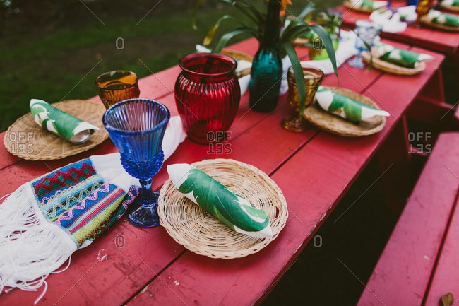 Red picnic table set for a Hawaiian themed wedding reception