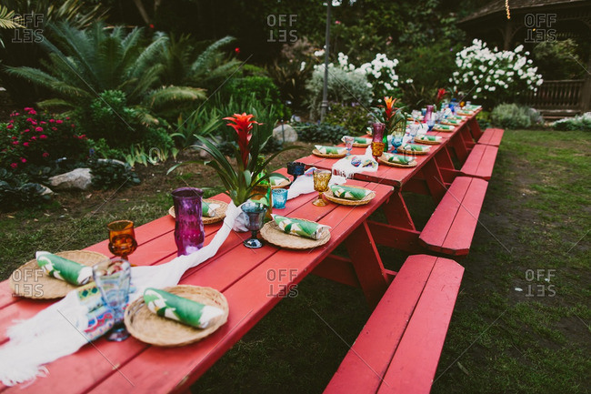 Picnic tables decorated for a Hawaiian themed wedding reception
