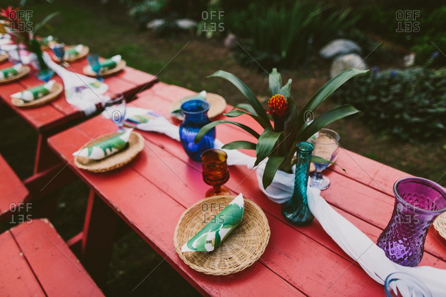 Colorful picnic tables decorated for a Hawaiian themed wedding reception