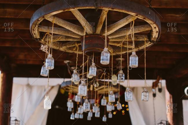 Antique jars hanging from a wagon wheel