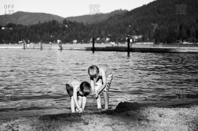 Two boys playing at edge of lake