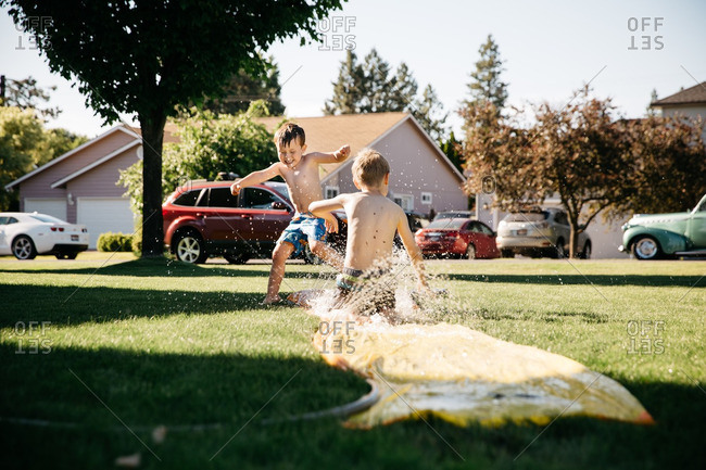 Two young boys playing on water slide in yard