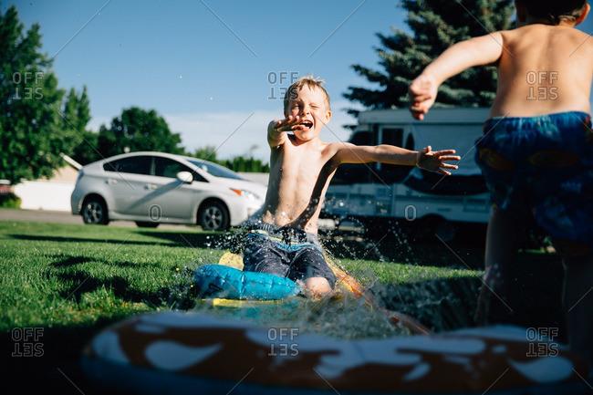 Boy sliding on a water slide in front yard