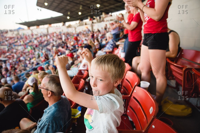 Young boy cheering in stands at baseball game