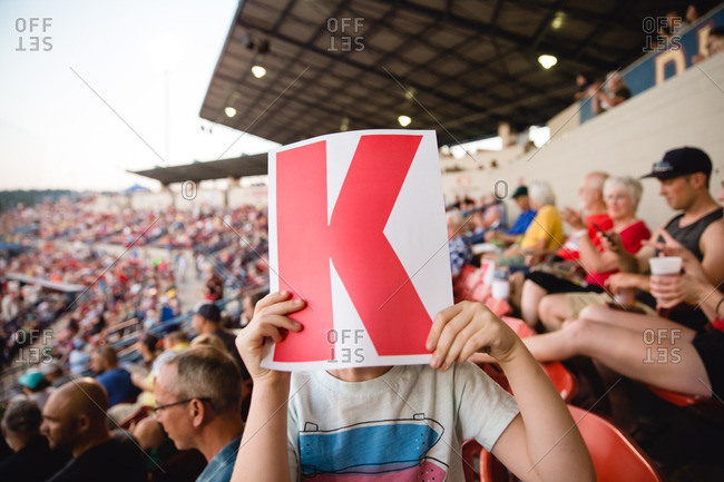 Child with a paper with letter in stands of sporting event