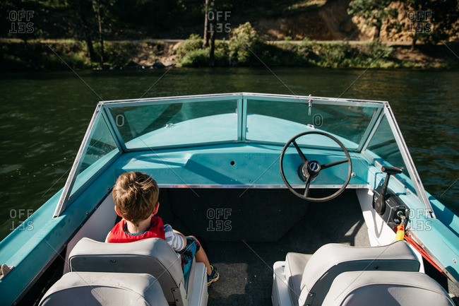 Young boy sitting in passenger seat of vintage boat in lake
