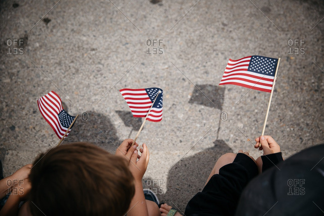 Overhead view of children holding American flags at parade