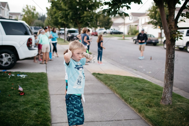 Boy covering his ears while standing with neighbors on sidewalk
