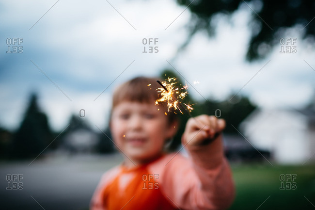Young boy with lit sparkler