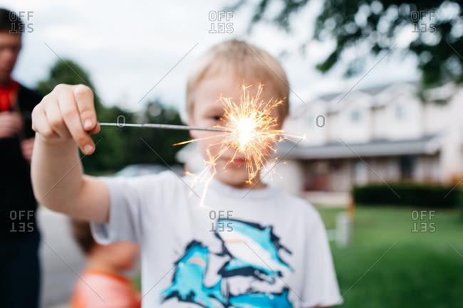 Boy watching lit sparkler