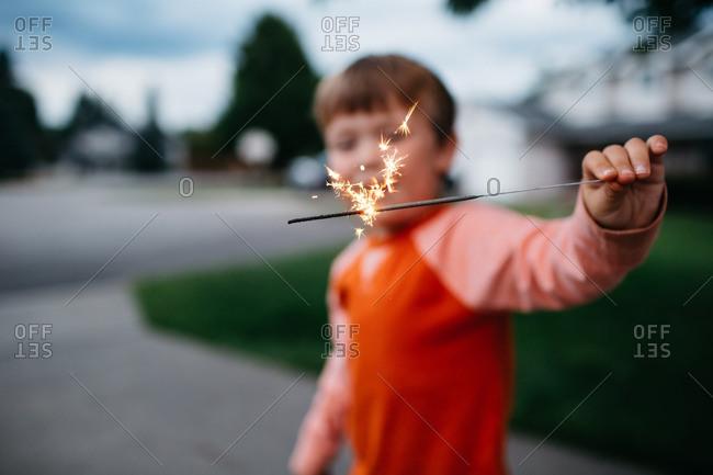 Boy holding a lit sparkler