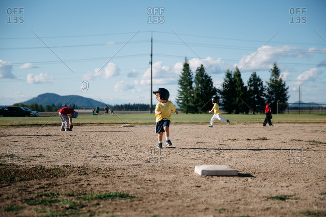 Young children run the bases in a t-ball game