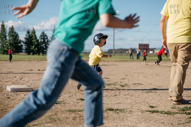 Little boy running bases in a t-ball game