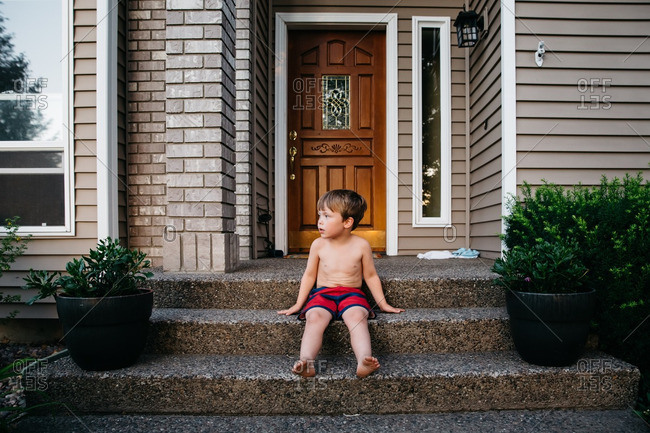 Shirtless boy sitting barefoot on front porch of house