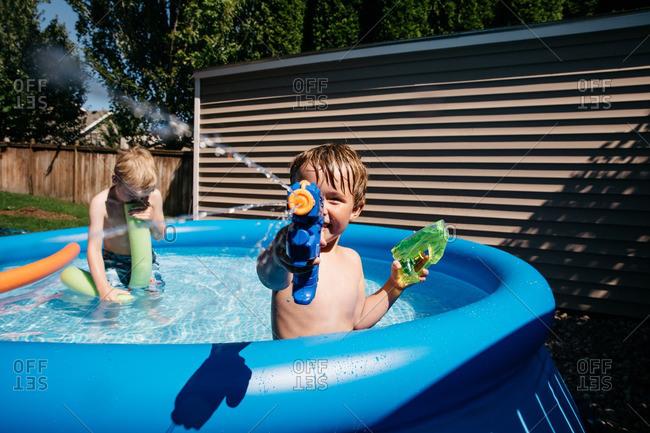 Boy squirting water in backyard pool